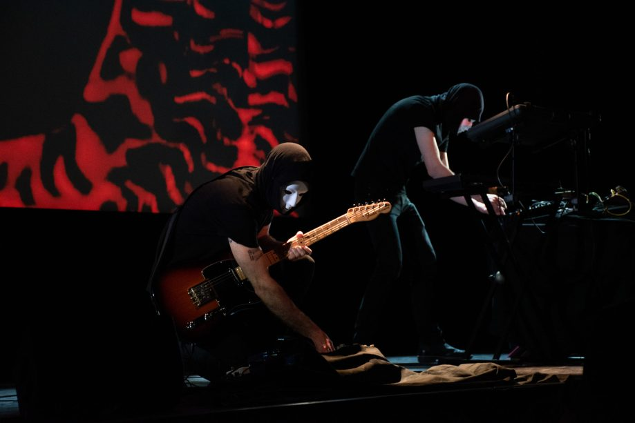 A masked guitarist leans down to adjust a pedal. Another masked musician is playing the keyboard in the background. They are standing in front of a screen with a psychedelic display.