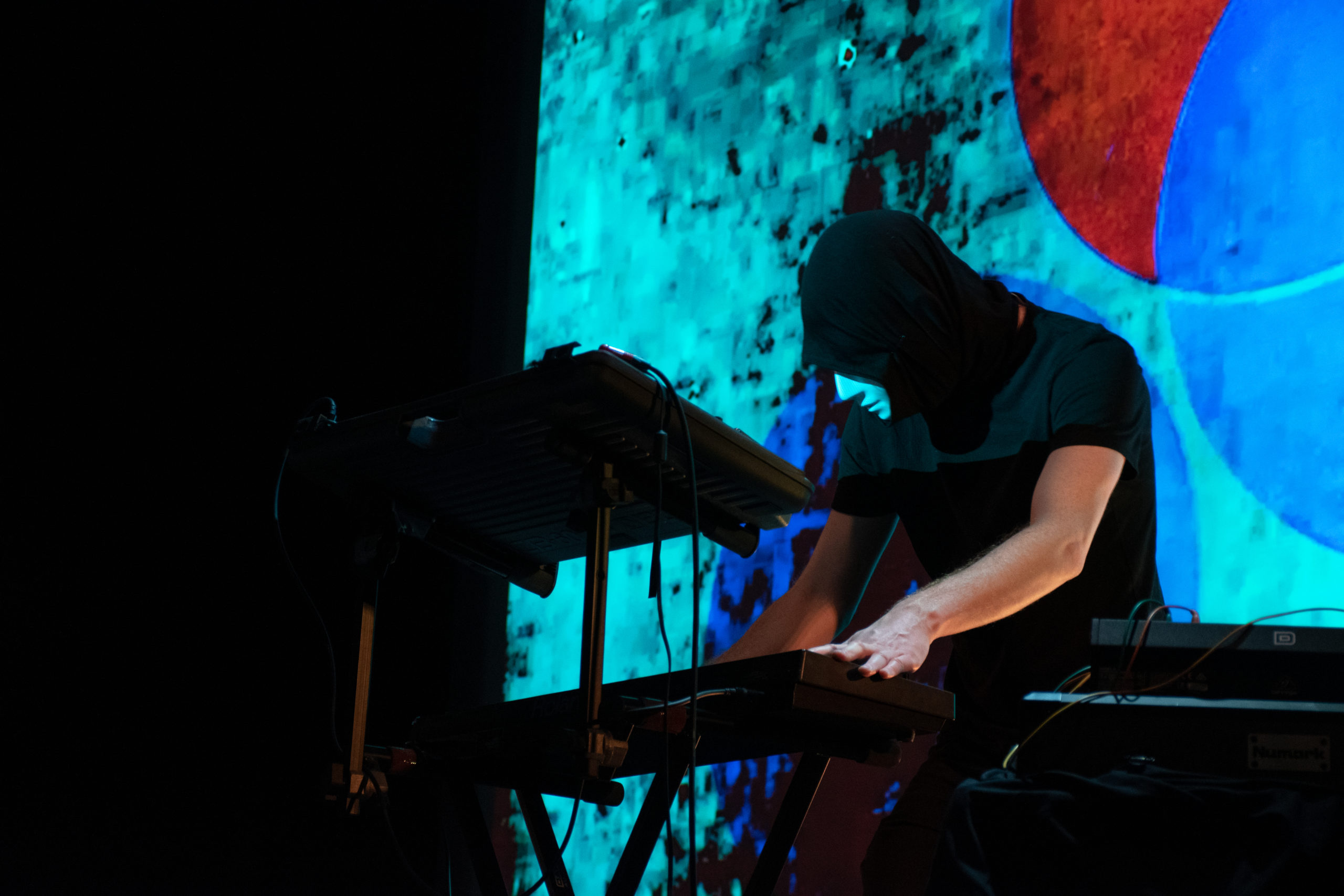 A masked musician plays the keyboard in front of a psychedelic display.