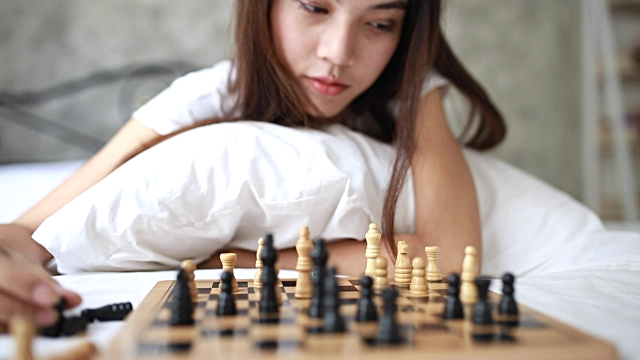 Young woman playing chess in her bed
