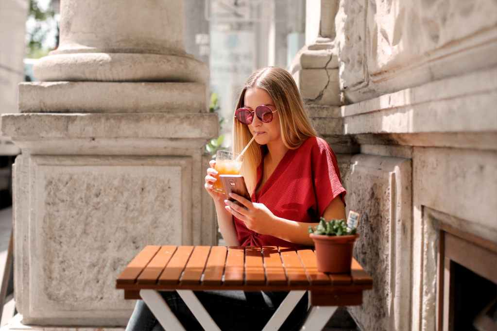 woman drinking while holding smartphone