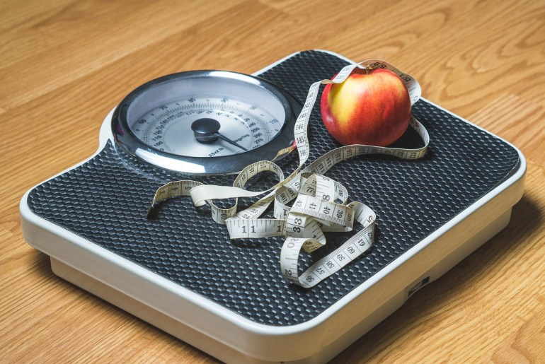 a scale with an apple and measuring tape on top