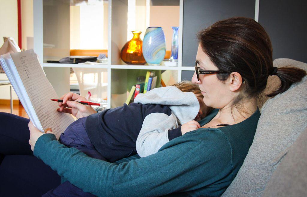 Madre trabajando con su hijx encima