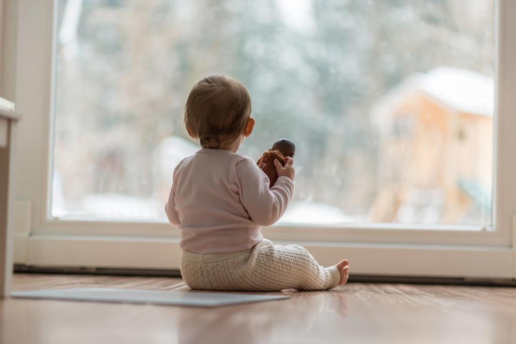 Bebé mirando por la ventana en ivierno