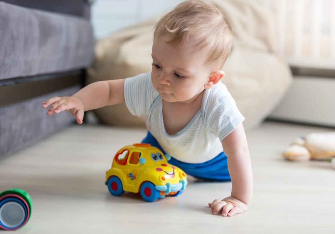 bébé qui rampe par terre pour attraper son jouet
