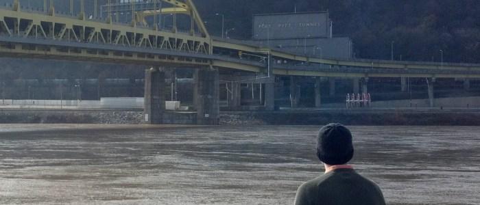 man staring at river