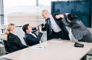 man lunging to hit coworker