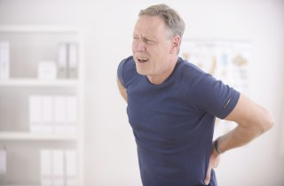 Man in pain holding back