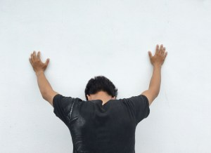 upset man with hands against wall and head hanging