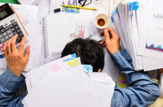 man slumped under a pile of papers