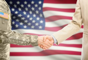 Military man shaking hands with business man