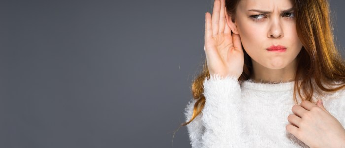 Girl with hand cupping ear