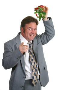 business man holding mistletoe over his head