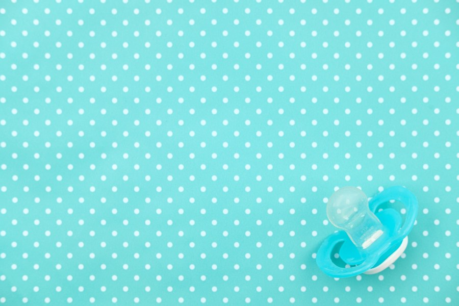 Top down photo of a pacifier / dummy against a torquise polka-dot background