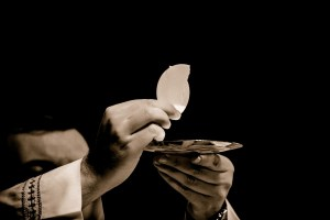 Catholic Priest presenting the Eucharist