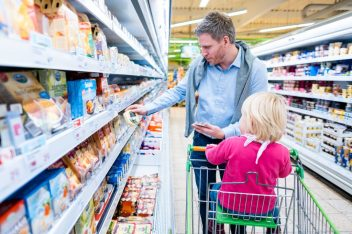 Man with child checking packaging labels in supermarket.
