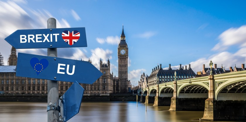Parliament of the United Kingdom and Westminster Bridge with Brexit and EU arrow signs.