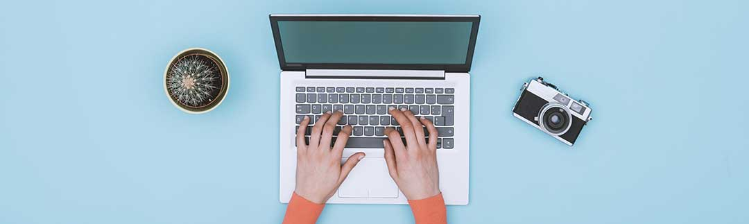 A lady writing on a computer as a mortgage is a written document.