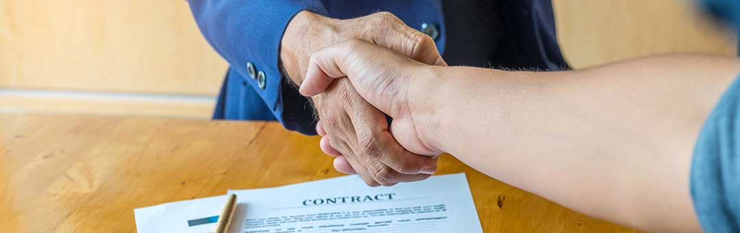 Shaking hands over an approved mortgage contract.