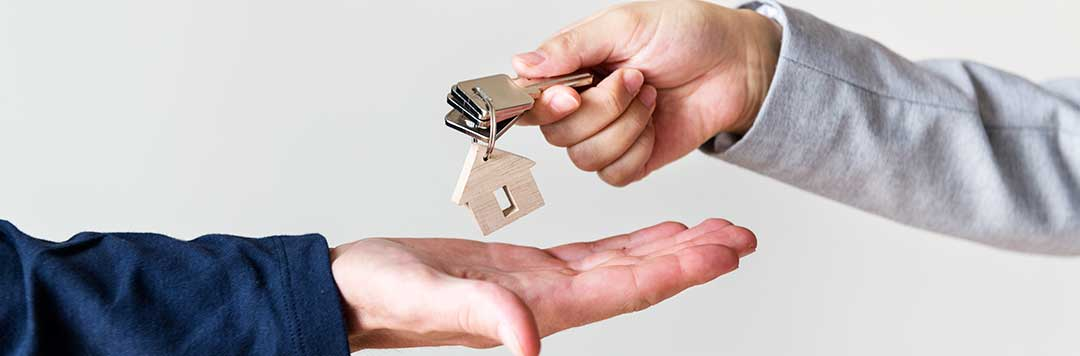 Two people exchanging housekeys to symbolize the transfer of ownership.