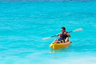 Father and son on a kayak ride in a tropical blue sea