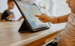 enfant qui touche une tablette sur laquelle apparaît une mappemonde