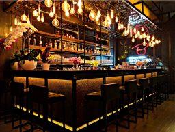Bar de nuit avec tabourets et boissons derrière
