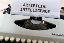 """Machine à écrire avec une feuille dedans sur laquelle il est écrit """"Artificial Intelligence"""""""
