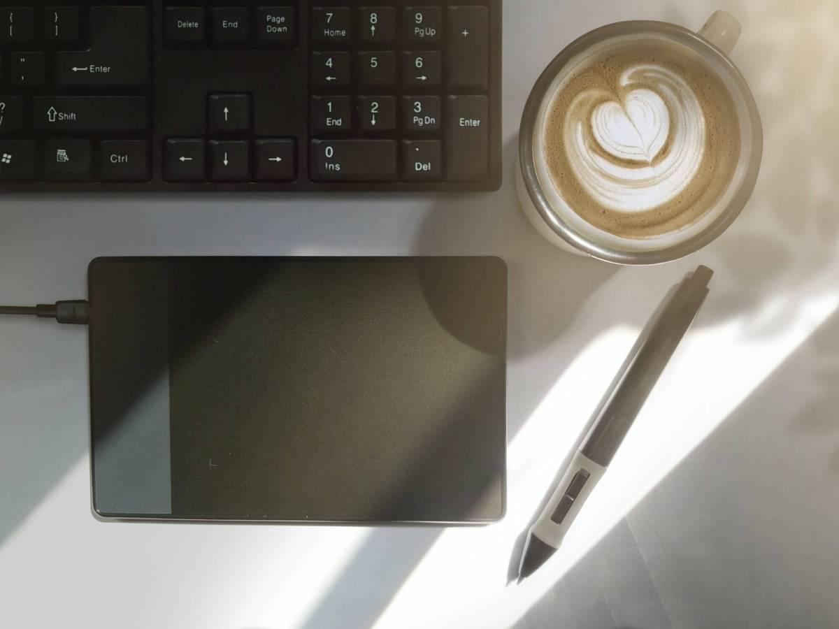 Café crème à côté d'un clavier d'ordinateur