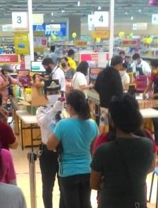 Gumagamit ng thermal scanner ang security guard ng isang supermarket sa Los Baños upang malaman ang temperatura ng mga mamimili bago sila payagang makapasok sa pamilihan. Larawang kuha ni Jyas Bautista