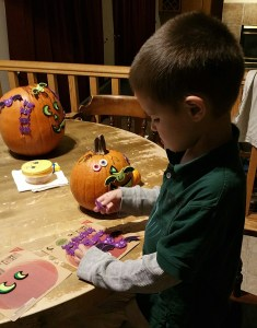 Four-year-old son decorating his pumpkin