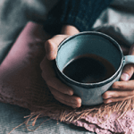 close up of a woman holding a cup of coffee