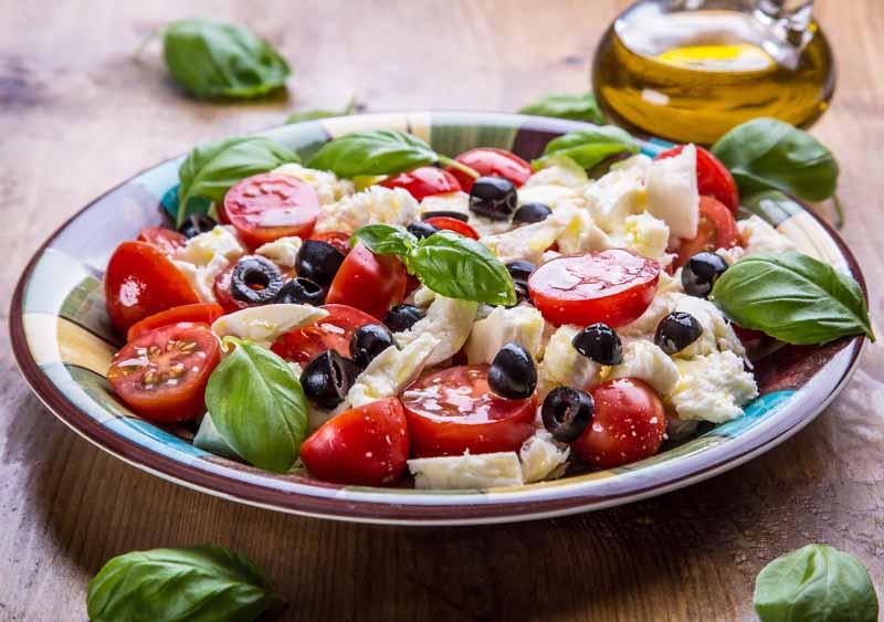 salata caprese italiana cu mozzarella, busuioc, rosii ulei de masline si masline negre, bucataria mediteraneana