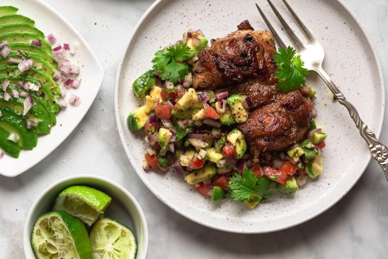 pulpe de pui dezosate la gratar cu salsa de avocado si rosii pe farfurii albe pe masa