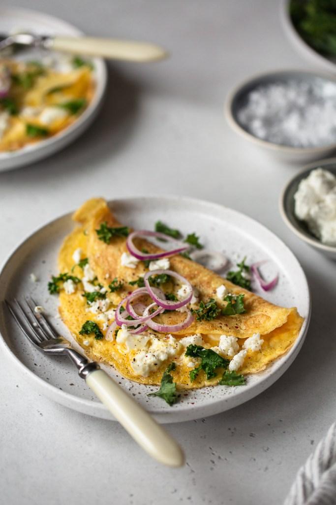 omleta cu branza feta, varza kale si ceapa rosie pe o farfurie alba pe masa