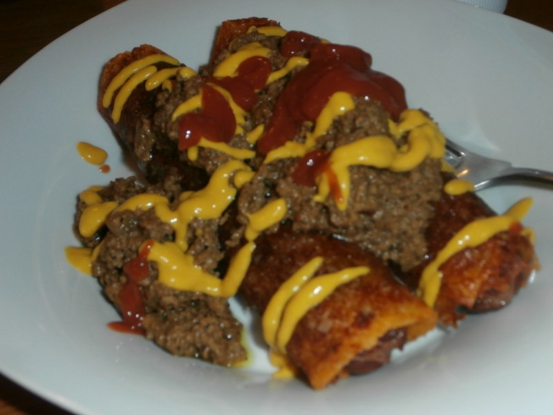 Two Perfectly Rolled hot dogs, wrapped in cheese with their toppings!