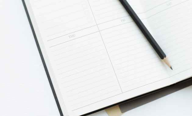 opened diary with pencil placed on desk