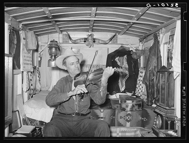 Mr. Bias playing the fiddle in his trailer home. He is a former cowboy who travels over the country. He has a small private income. Weslaco, Texas