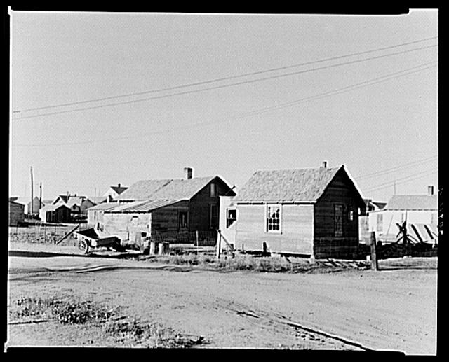 """Houses that were moved to town from the country by General Jackson, former farmer now living in Plentywood, Montana. At one time he had 125 cattle; the other day he sold last cow. Buildings left in the country were usually wrecked or the lumber stolen for building or fuel. Lumber is very costly in the section, for all of the name """"Plentywood"""""""
