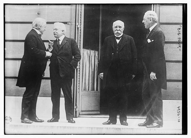 group of four men standing outside a building