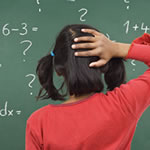 Young femaile student having difficulty with math problem on chalkboard displaying symptoms of Dyscalculia.