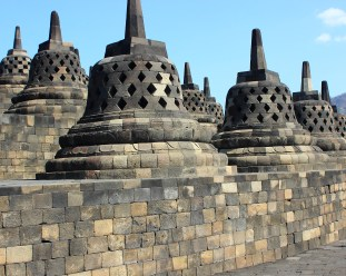 Borobudur temple, Indonesia. Each of the stone 'bells' contains a Buddha. It is said to be good luck if you can reach in a touch one