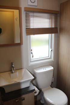 ABI Roxbury holiday home - The shower room has a ceramic washbasin and a two door vanity cupboard plus an extractor fan in the wall.