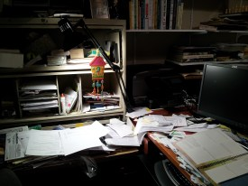 Picture of a desk with paper piled all over.