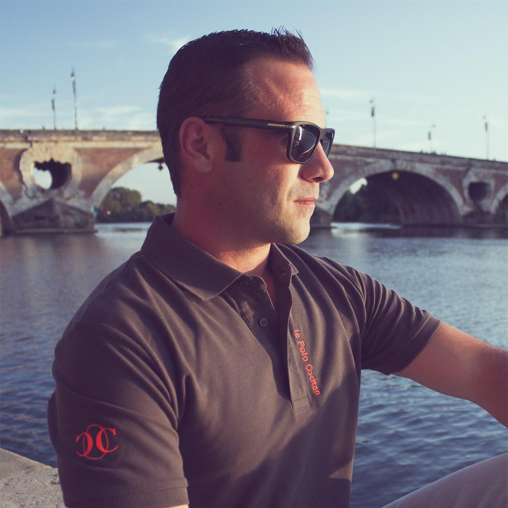 """Homme portant un polo """"le polo occitan"""" devant le pont neuf à Toulouse"""