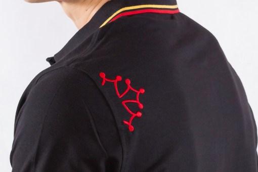 Polo noir avec croix occitane rouge, détail de la croix occitane sur l'épaule