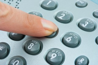 Phone keypad and woman finger - abstract communication backgroun