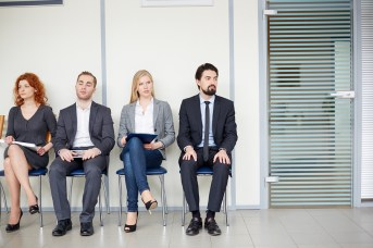 Portrait of several business associates sitting on chairs by off