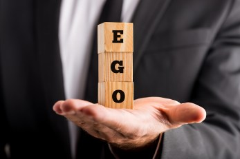 Businessman Holding Wooden Alphabet Blocks Reading - Ego