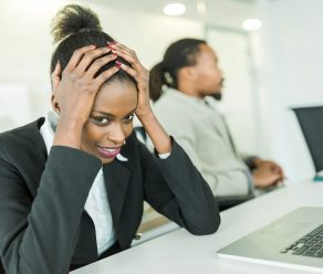Young Stressed Businesswoman Battling With A Headache During A B