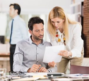 Young businesswoman sharing information with businessman. Young